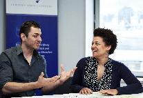 Zwei Menschen im Gespräch vor Tafel
