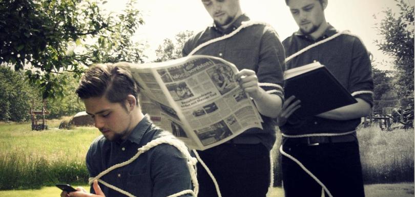 Mann liest Buch, dann Zeitung, dann auf Smartphone