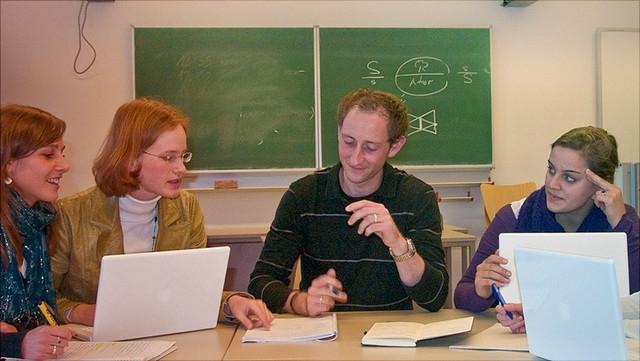 Studierende und Lehrender sitzen zusammen und besprechen etwas.