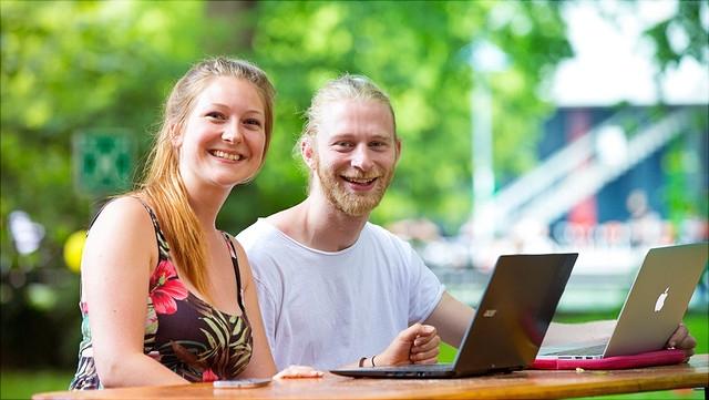 Studierende mit Laptops im Freien