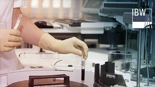Behandschuhte Hände hantieren mit Reagenzglas.
