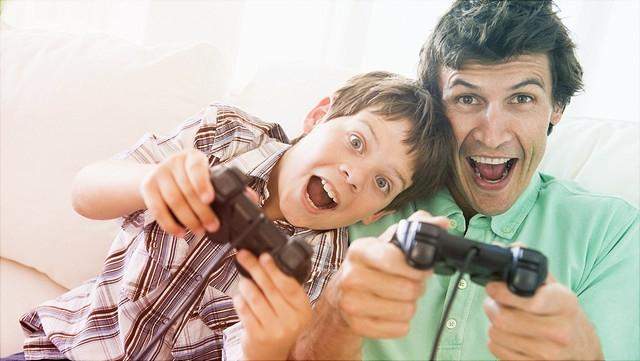 Vater und Sohn spielen begeistert ein Computerspiel.