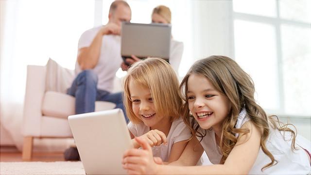 Kleine Mädchen mit Tablet, Eltern im Hintergrund