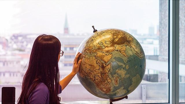Frau betrachtet Globus.