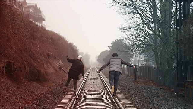 Zwei Jugendliche laufen auf Schienen in den Nebel.
