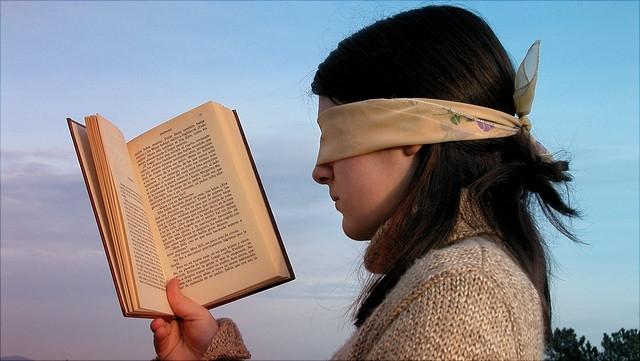 Mädchen liest mit verbundenen Augen.
