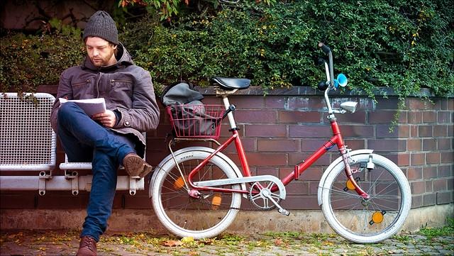 Student auf Bank mit Fahrrad