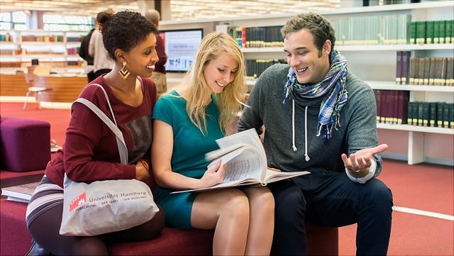 Studierende in Bibliothek sprechen über ein Buch.