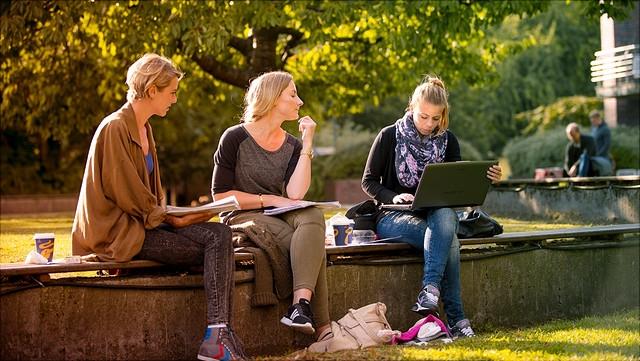 Studierende auf einer Bank im Freien