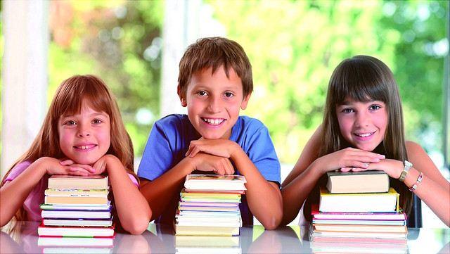 Drei Kinder, gestützt auf Bücherstapel