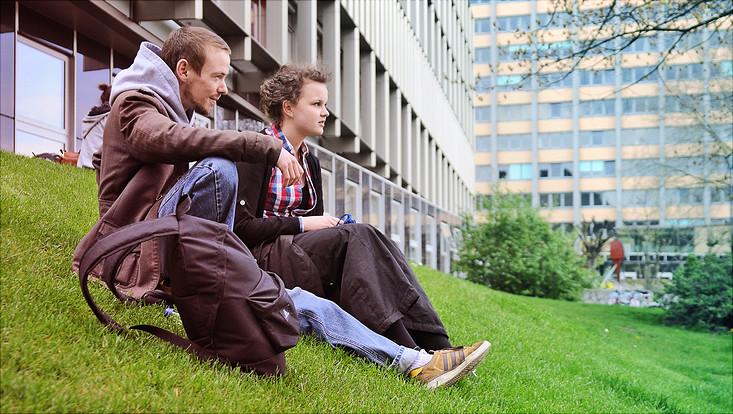 Zwei Studierende sitzen auf der Wiese