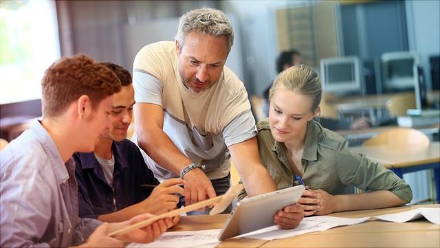 Lehrer erklärt älteren Schülern etwas am Tablet.