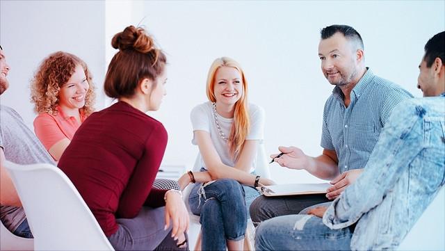 Gruppe junger Menschen im Gespräch mit Lehrer.