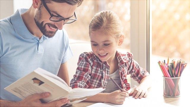 Vater schaut sich mit Tochter Schulbuch an.