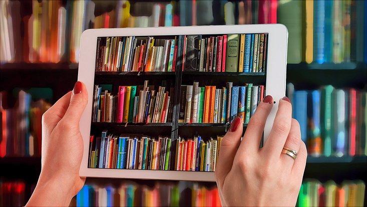Tablet fotografiert ein Buchregal