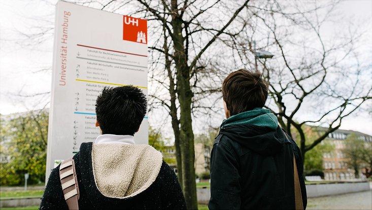 Studierende vor Campus-Plan