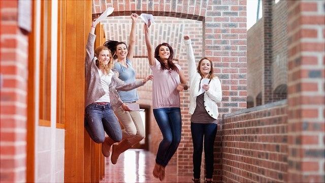 Ältere Schüler springen in die Luft mit Zeugnissen in der Hand.