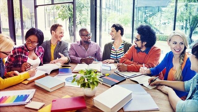 Junge Erwachsene sitzen am Tisch und arbeiten in Kleingruppen.
