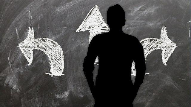 Männlicher Schatten vor einer Tafel mit drei Pfeilen