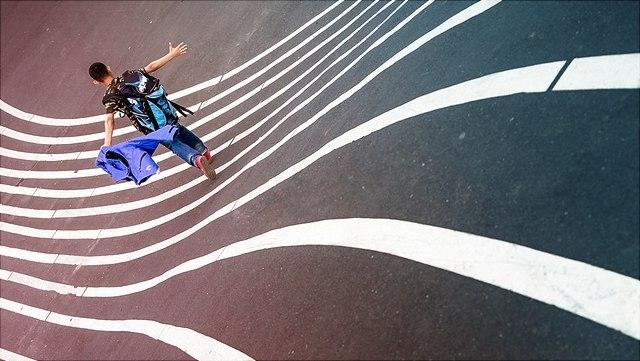 Junge läuft auf welligen Linien auf der Straße.