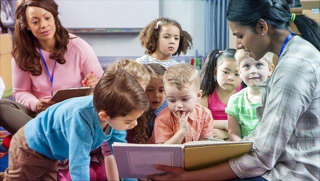 Kinder verschiedener Ethnien hören Erzieherin im Kindergarten zu.