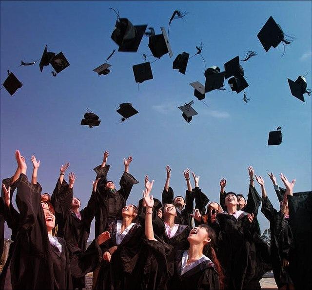 AbsolventInnen werfen ihre Diplomhüte in die Luft