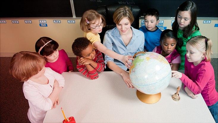 Kinder sehen sich in einem Klassenzimmer einen Globus an.