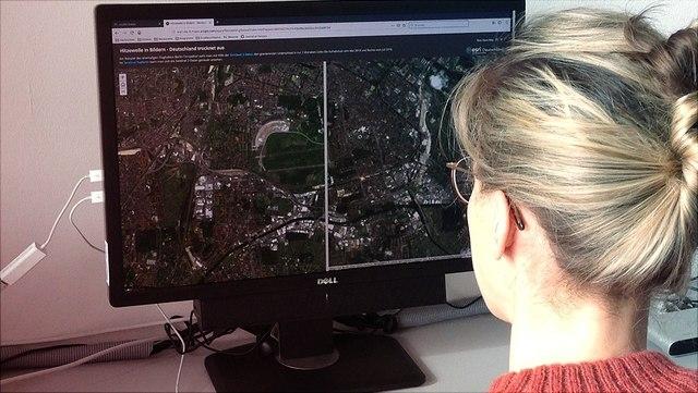Frau arbeitet mit Geographie-Programm an Computer.