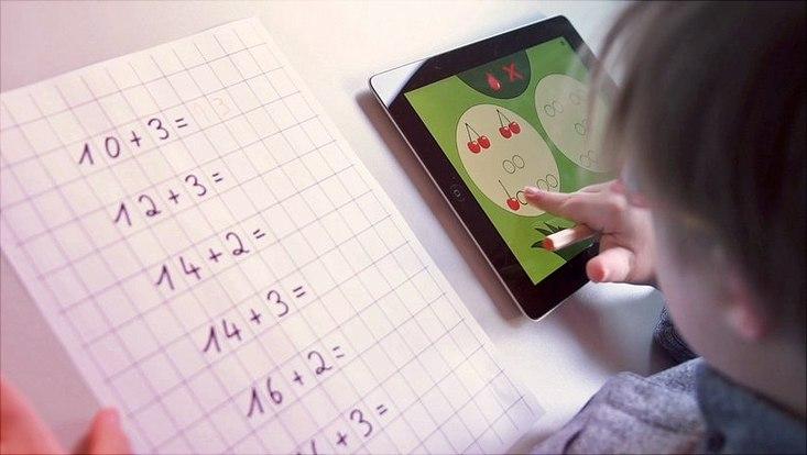 Ein Kind löst seine Mathematikaufgaben im Mathematikheft mit Hilfe einer auf einem Tablet geöffneten App, in der es Kirschen anklickt.