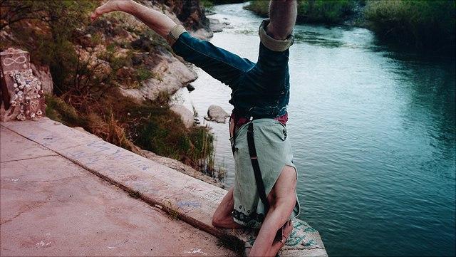 Kopfstand an Klippe über einem Fluss
