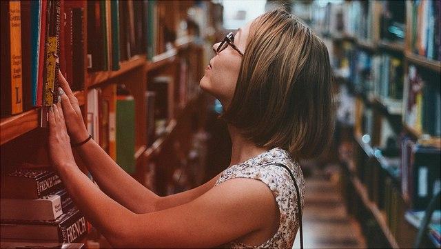 Frau in Bibliothek vor Bücherregal
