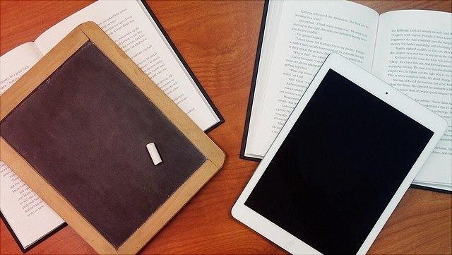 Tafel mit Stück Kreide auf Buch, Tablet auf Buch