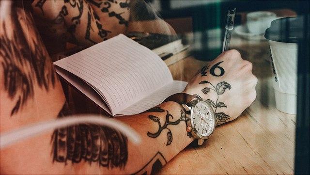 Tätowierter Arm mit Uhr schreibt in Notizbuch