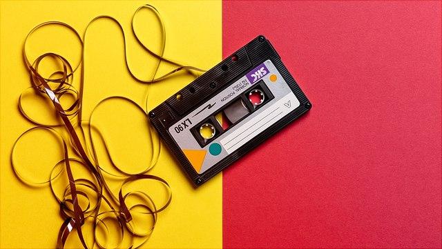 Musikkassette mit ausgefädeltem Band auf rotem und gelbem Untergrund