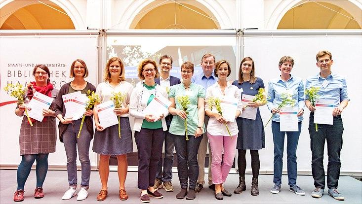 Die Preisträgerinnen und Preisträger der ausgezeichneten Lehrprojekte stehen auf der Bühne im Lichthof.