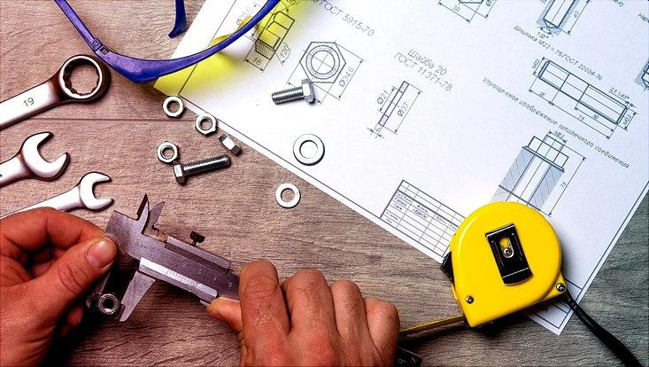 Bild von Händen mit Werkzeugen und technischer Zeichnung
