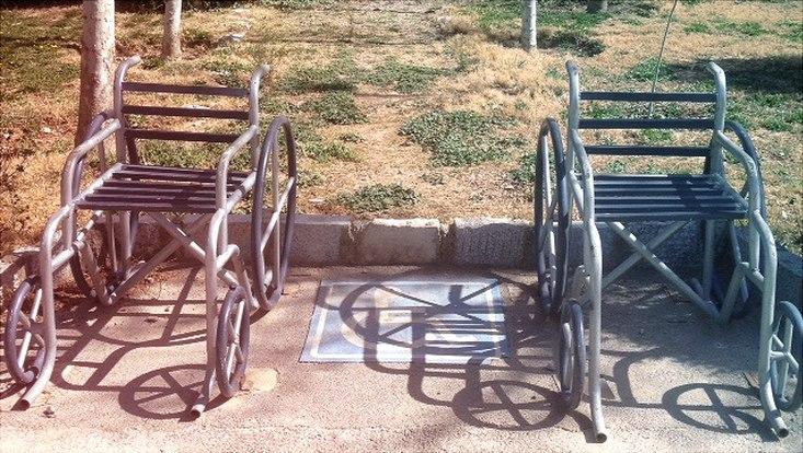 Zwei leere Rollstühle stehen auf der Straße.