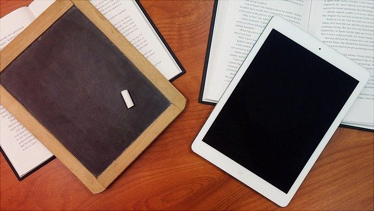 Tafel und Tablet liegen nebeneinander auf einem Tisch.
