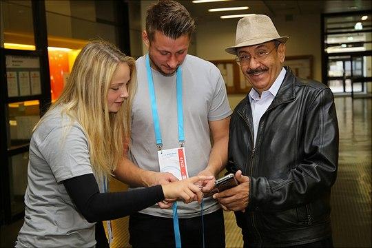 Drei Teilnehmende mit Smartphone