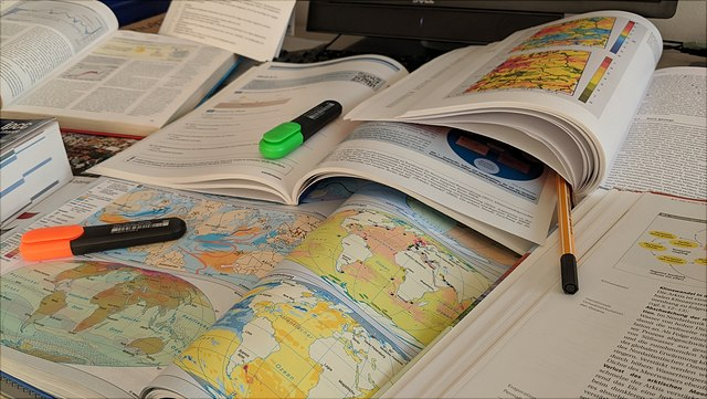 Bücher, Landkarten und Stifte auf einem Schreibtisch