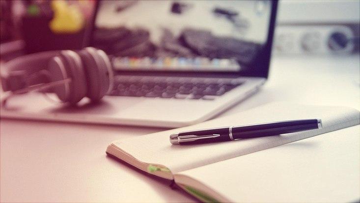 im Hintergrund ist ein Laptop zu sehen, im Vordergrund ein Notizbuch mit Füller