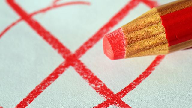 Ein roter Buntstift und ein gemaltes Kreuz in einem Kreis sind zu sehen.