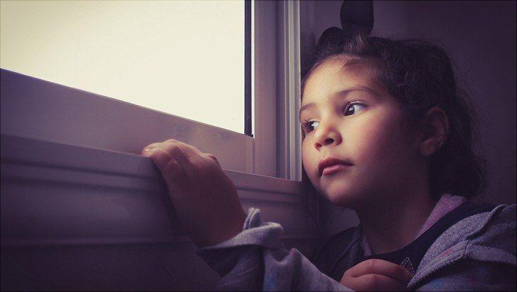 Mädchen schaut traurig über den Fensterrand.