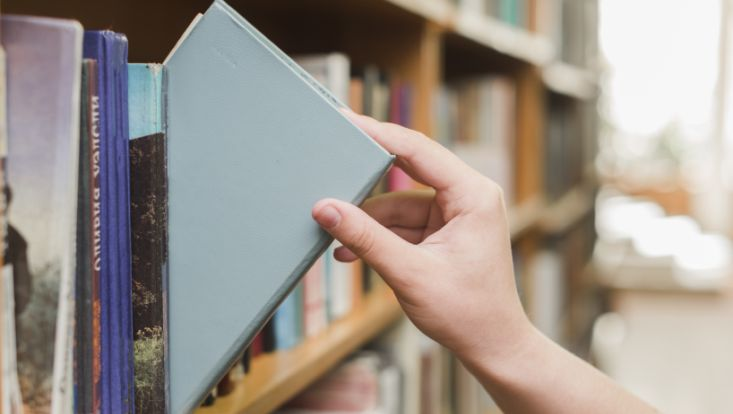 Hand nimmt Buch aus Regal