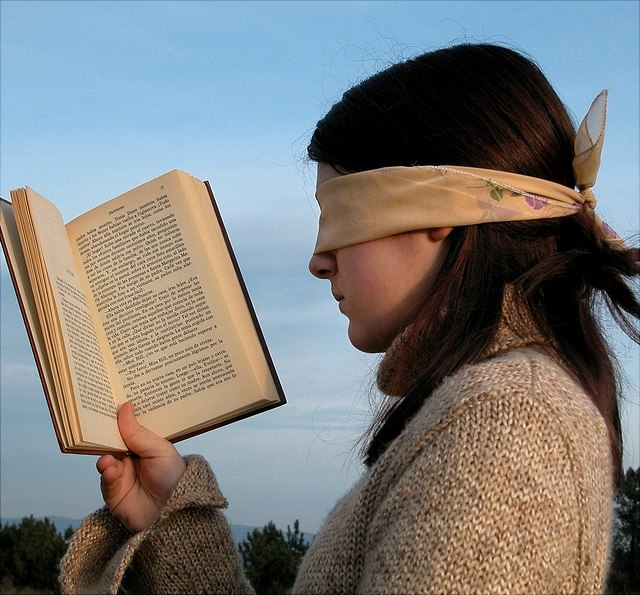 Girl reads with her eyes covered