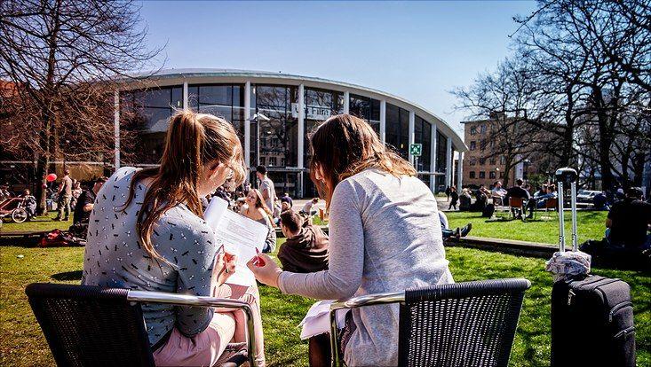 Studierende auf der Wiese vor dem Audimax