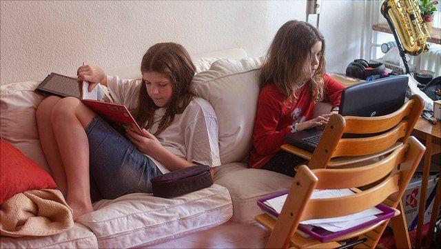 Zwei Kinder auf dem Sofa beim Fernunterricht während der Corona-Schulschließungen