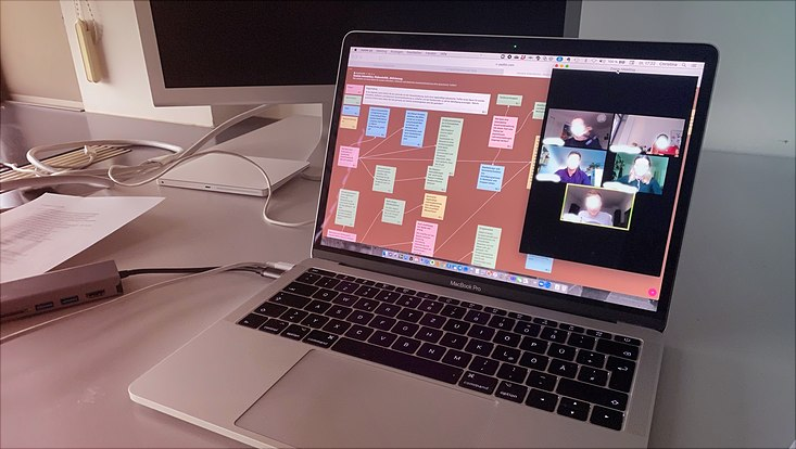 Auf einem Tisch steht ein Laptop, auf dem ein padlet und ein Videokonferenz-Fenster zu sehen sind.