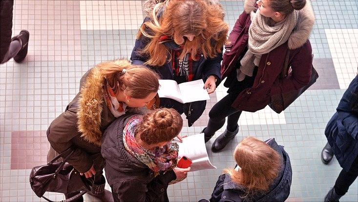 Studentinnen lesen Informationen der Universität.