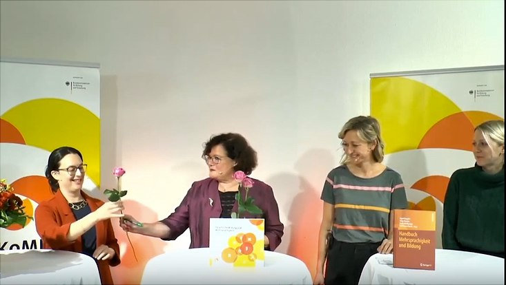 Die Organisatorinnen stehen an zwei Tischen; Ingrid Gogolin überreicht Blumen.